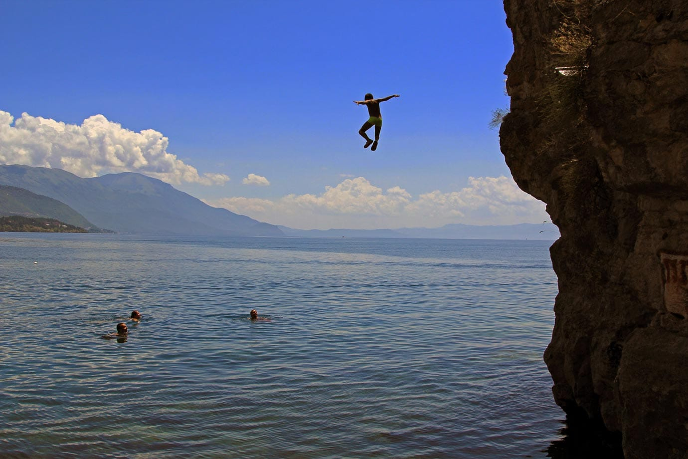 A young boy cliff jumping at Kaneo Beach