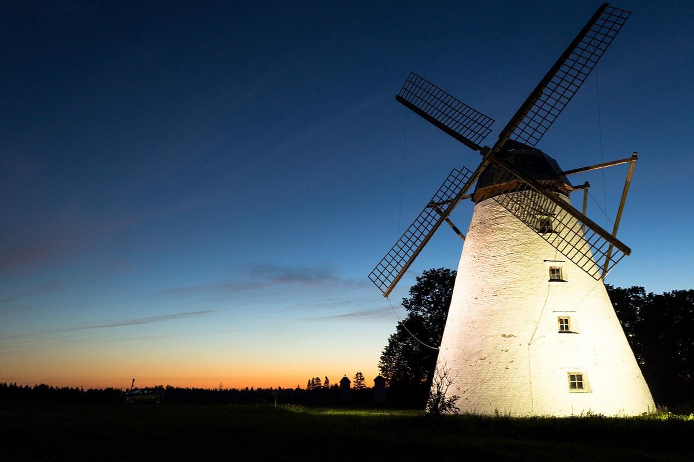 Windmill lit up at night in Estonia